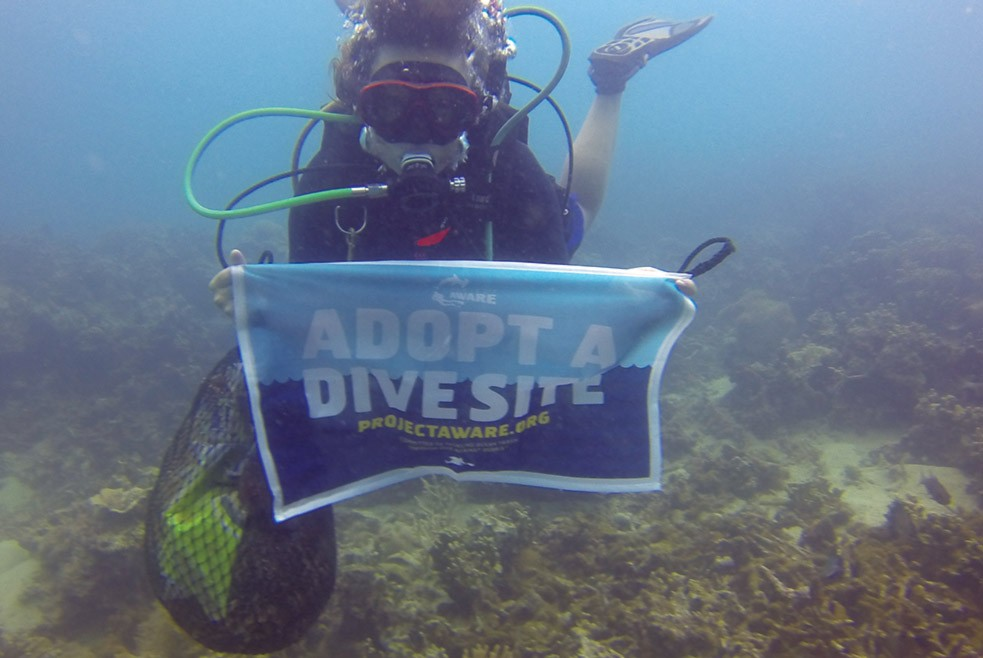 Nic Emery diving with Adopt a Dive Site banner