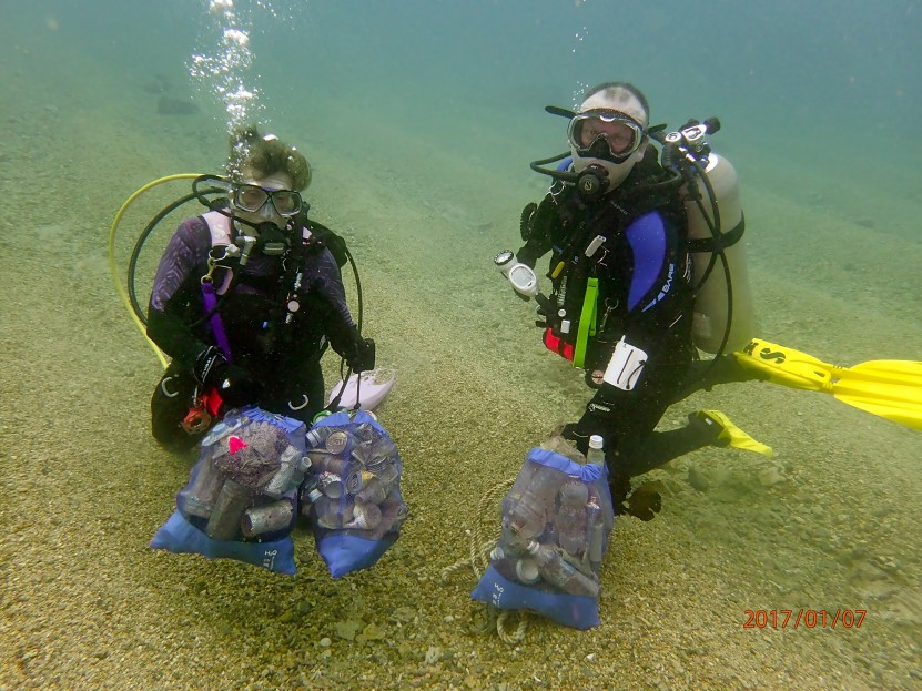 Divers Underwater with Bags of Debris