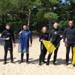 Seven volunteer divers are lined up on the beach after the cleanup!